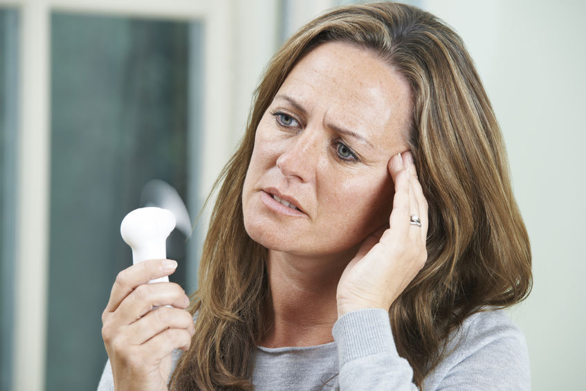 54861242 - mature woman experiencing hot flush from menopause